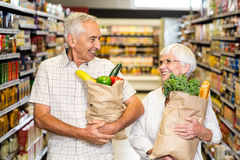 Smiling senior couple holding grocery bags Royalty Free Stock Photo