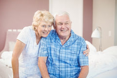 Smiling senior couple at home. Smiling senior couple sitting on bed at home Stock Photo