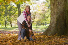 Smiling senior couple hugging outdoors amidst autumn leaves stock photos
