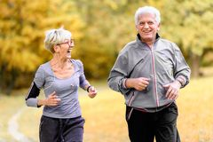 Smiling senior couple jogging in the park. Smiling senior active couple walking, jogging and talking in the park royalty free stock images