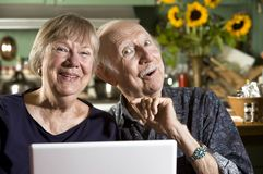 Smiling Senior Couple with a Laptop Computer royalty free stock image