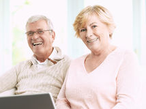 Smiling Senior Couple with Laptop Stock Images