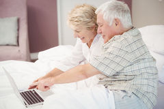 Smiling senior couple laughing while using laptop Stock Photo