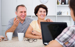 Smiling senior couple listening to young woman Royalty Free Stock Image
