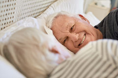 Smiling senior couple looking at each other in bed Stock Photos