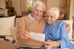 Smiling senior couple looking at old photos together at home Royalty Free Stock Photography