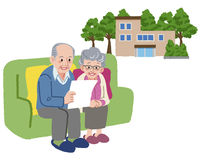 Smiling Senior couple looking at paper with retirement home in background Stock Images
