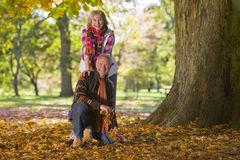 Smiling senior couple outdoors amidst autumn leaves Stock Photo