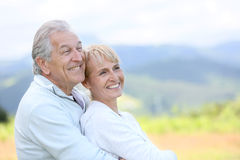 Smiling senior couple outdoors enjoying. Portrait of senior couple looking towards the future Royalty Free Stock Photos