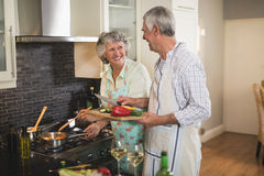 Smiling senior couple preparing food together in kitchen Royalty Free Stock Images