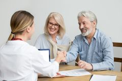 Smiling senior couple and realtor handshaking making real estate. Deal, older men and mortgage broker shaking hands, aged family buyers agree to make investment stock image