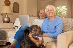 Smiling senior couple relaxing with their dog at home Royalty Free Stock Image