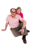 Smiling senior couple seated on floor. Posing Royalty Free Stock Photos