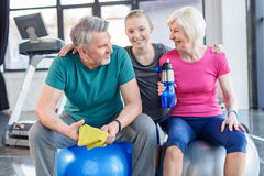 Smiling senior couple sitting on fitness balls and smiling girl Royalty Free Stock Photography