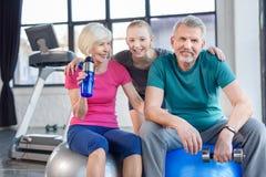 Smiling senior couple sitting on fitness balls and smiling girl Royalty Free Stock Image