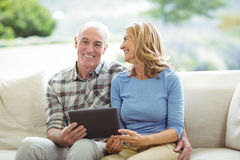 Smiling senior couple sitting on sofa with digital tablet in living room Royalty Free Stock Photos