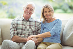Smiling senior couple sitting together on sofa in living room Stock Photos