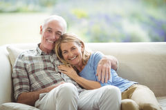 Smiling senior couple sitting together on sofa in living room royalty free stock photos