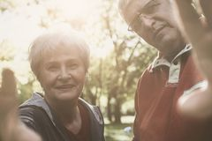 Senior couple in sports clothing holding a camera togeth royalty free stock image