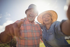 Smiling senior couple standing in lawn on a sunny day. Portrait of smiling senior couple standing in lawn on a sunny day Stock Images