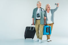 Smiling senior couple with traveling bags making selfie on smartphone Stock Image