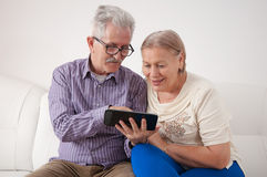 Smiling senior couple using a digital tablet. Smiling senior couple spend time together and using a digital tablet Stock Images