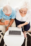 Smiling senior couple using laptop Stock Images