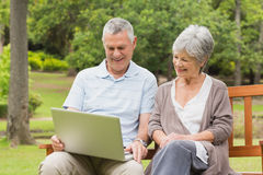 Smiling senior couple using laptop at park Royalty Free Stock Photography