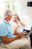 Smiling senior couple using laptop and smartphone Stock Image