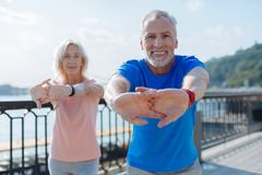 Smiling senior couple warming up together royalty free stock image