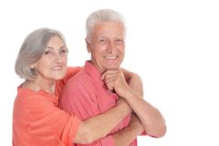 Smiling senior couple wearing bright clothing on white background. Smiling senior couple wearing bright clothing isolated on white background stock image