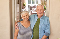 Smiling senior couple welcoming at their front door stock image