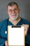 Smiling Mature Doctor Displays a Blank Clipboard. A smiling senior doctor or nurse displays a blank clipboard Royalty Free Stock Photo
