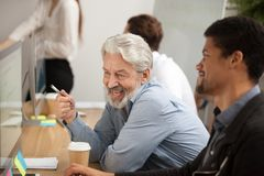 Smiling senior employee discussing email with african colleague. At workplace, happy older worker talking to black coworker joking about online computer work Stock Photos