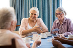 Smiling senior female friends playing cards. While having coffee at table in nursing home Royalty Free Stock Photography