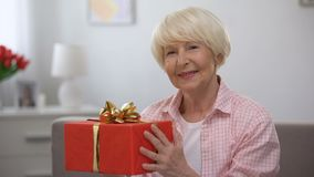 Smiling senior female holding gift box, happiness, womens day celebration. Stock footage stock video footage