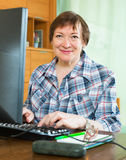 Smiling senior female using keyboard Stock Photography
