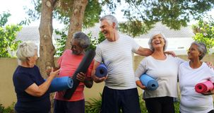Smiling senior friends holding exercise mat and interacting with each other 4k