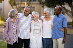 Smiling senior friends standing with arms around. Outside nursing home Stock Photography