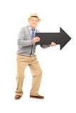 Smiling senior gentleman holding an arrow pointing to the right Stock Photos