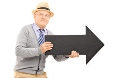 Smiling senior gentleman holding a big black arrow pointing to t Royalty Free Stock Image