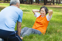 Smiling senior grandmother doing sit-ups in the park Stock Images