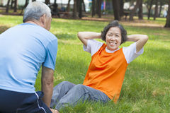 Smiling senior grandmother doing sit-ups in the park Royalty Free Stock Photos