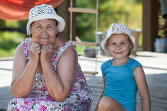 Smiling senior grandmother and happy grandchild are on summer veranda Stock Photography