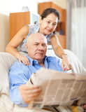 Smiling senior guy with newspaper and mature wife Royalty Free Stock Image