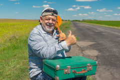 Smiling senior hiker having short rest on a roadside with ancient green suitcase and mandolin Stock Images