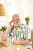 Smiling senior holding medication Stock Photography
