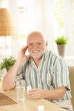 Smiling senior holding medication Stock Photography