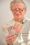 Smiling senior holding winnings. Royalty Free Stock Photo
