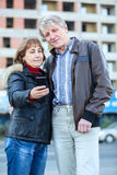 Smiling senior husband and wife looking at cellphone screen together Stock Photo